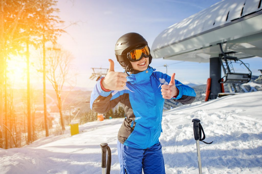 Portrait of young female skier at ski resort smiling and showing thumbs up. Winter sports concept. Woman is wearing blue jacket and blue pants, helmet and orange goggles.