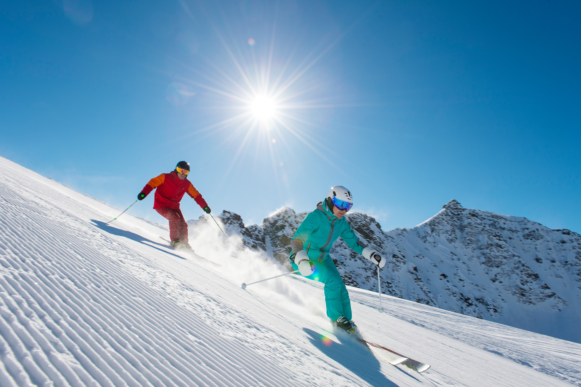 two skiers on sunny piste