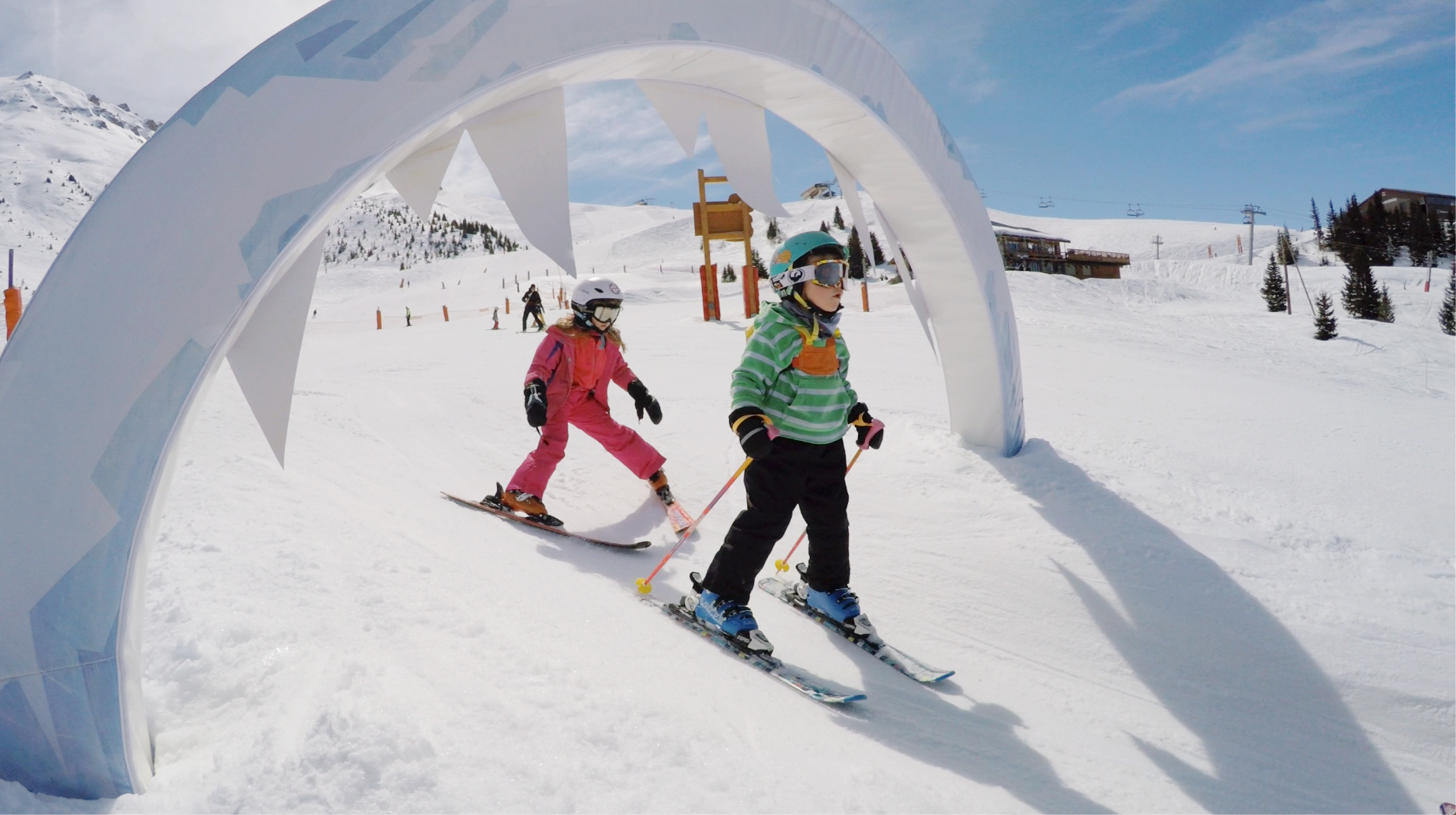 two children having fun skiing under an arch during ski lessons