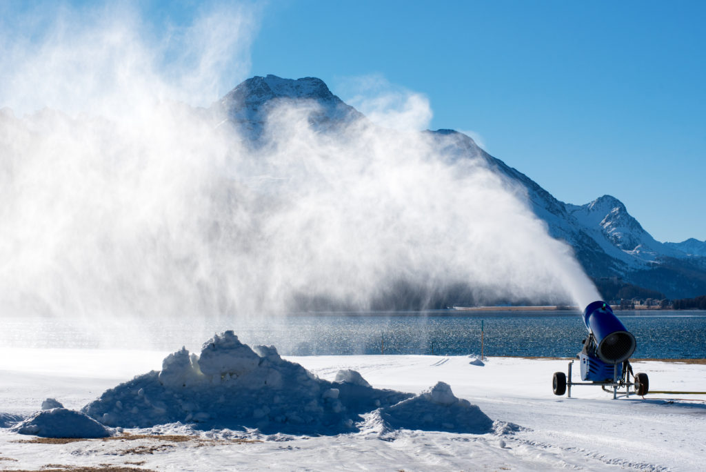 Artificial snow blown by snow gun standing near water on snowbound ground in sunny day with blue sky